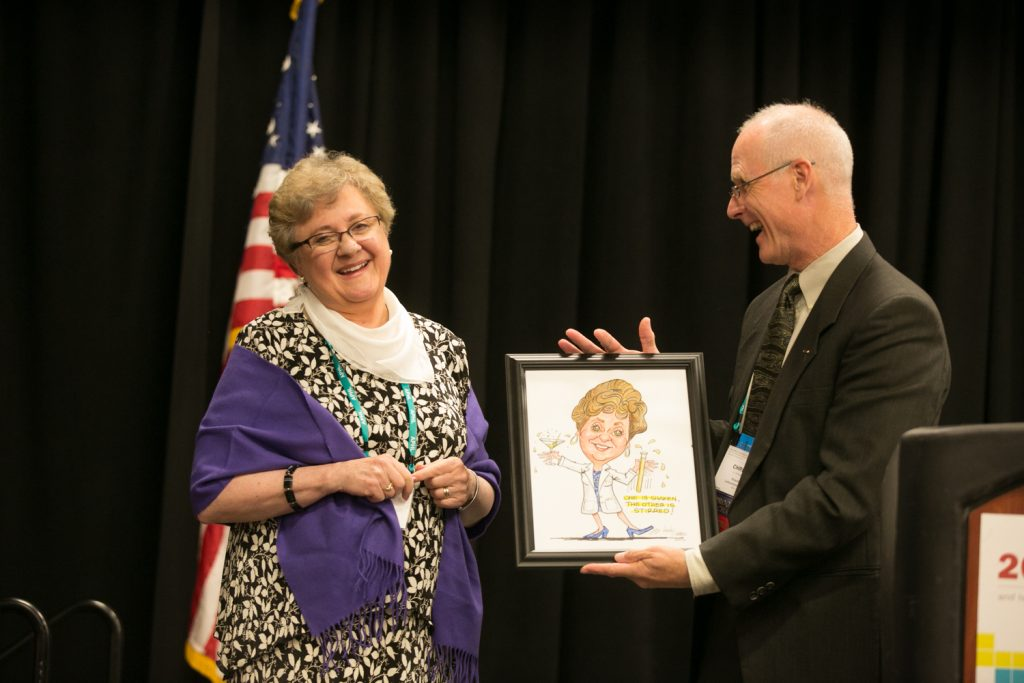In-coming board president, Chris Whelen, gives Judy Lovchik, past president, a parting-gift