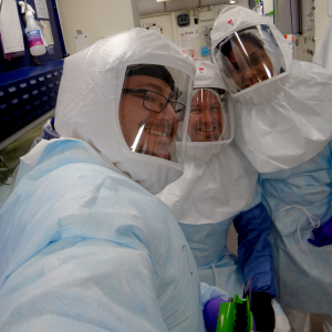 Three Humboldt County Public Health Laboratory scientists dressed in protective gear take a selfie in the laboratory.