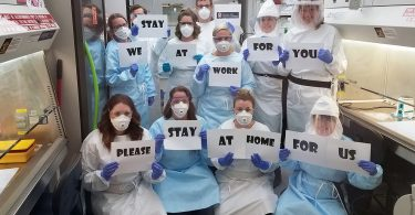 """Wisconsin public health lab staff hold signs that say """"We stay at work for you; please stay at home for us"""""""