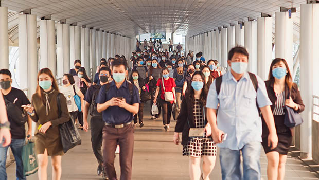 People in a public transportation hub, checking their phones