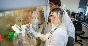 An APHL-CDC Fellow works under a hood in a laboratory as her supervisor looks on.